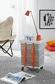 Mobiler Beistelltisch aus Zeitschriftenstapel, Holzplatten und Gurten, darauf Tischlampe und Kaffeebecher