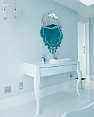 Elegant designer bathroom with ornate mirror above sink mounted on postmodern console table
