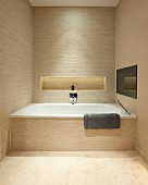 Fitted bathtub in designer bathroom with beige strip tiles; shelf niche with indirect lighting in back wall