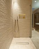 Begehbare Dusche in Designerbad mit Fliesen im Naturlook; Ablagenische mit indirekter Beleuchtung in der Rückwand