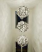 Three-part modern pendant lamp in tall hallway