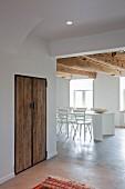Minimalistischer, weißer Essbereich unter rustikalen Holzbalken in renoviertem Ambiente