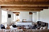 Loungebereich mit weißem Gaskamin, Kaminfeuer und sichtbaren rustikalen Balken