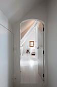 Einblick in renoviertes weißes Dachgeschosszimmer mit Sprossenfenster