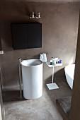 Weißes Standwaschbecken mit Standarmatur in reduziertem Designerbad mit schwarzem Hängeschränkchen und Betonboden