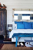 Vintage mirror on white wooden wall above bed with blue and white patterned scatter cushions and blue bench at foot