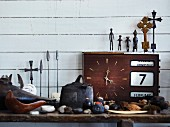 Still-life arrangement of holiday souvenirs and metal figurines on top of old clock against white wood-clad wall