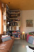 Leather couch in front of L-shaped bookcase made from reclaimed boards in corner of room with patchwork beanbag