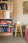 Retro Holzhocker mit Tischleuchte neben Regal aus wiederverwendeten Brettern