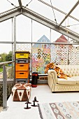 Patterned leather pouffe and metal frame holding colourful plastic crates against decorated glass façade on gallery in former greenhouse