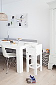 Dining area with white metal mesh pinboard in family-friendly interior with white highchair and basket of toys