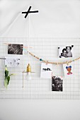 Photos and bead necklace hung on white metal mesh used as pinboard and minimalist pendant lamp stuck on wall with black tape