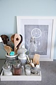 Still-life arrangement of various retro kitchen utensils on white wooden tray in front of picture of dream-catcher