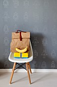 Bag, yellow lunch box and banana on white Eames Chair against grey wallpaper with pattern of robots