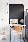 Retro chair, desk, toy dinosaurs, painted chalkboard on wall and pendant lamp with yellow power cable