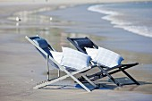 Two deckchairs with cushions on seashore