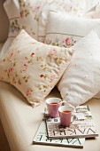 Magazines and teacups on bed with romantic floral bed linen