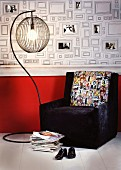 Dark armchair with photo motifs on cushion and standard lamp in front of wallpaper with pattern of picture frames