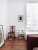 Schlicht eingerichtetes Schlafzimmer mit Holzboden, antikem Stuhl und Holztischchen als Nachttischablage