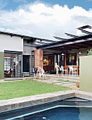 Pool, children playing with dog and roofed terrace in courtyard of bungalow