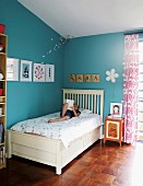Child on white bed in corner of blue-painted room with framed pictures and letters on wooden boards on walls