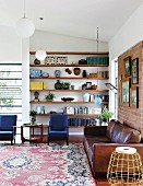 Brown leather couch and two blue armchairs in front of floating shelves in niche in corner of living room