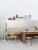 Modern dining table, wooden chair, stools and bench against half-height wall panel with elegant crockery on top