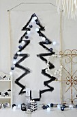 White length of fabric decorated with black painted Christmas tree and fairy lights on wall