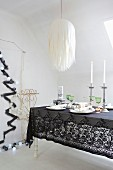 Festively decorated Christmas dining table with black lace tablecloth under paper lampshade