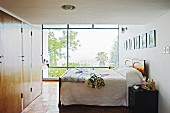 Box-spring bed and wooden fitted wardrobes in bedroom with view of garden through glass wall
