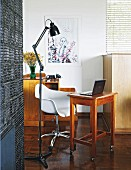 Black, metal, retro standard lamp next to shell chair and laptop on side table with castors