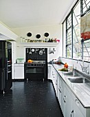 Black and white kitchen with long counter below bank of windows and black vinyl floor