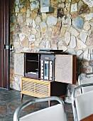Retro hifi cabinet against stone-clad wall