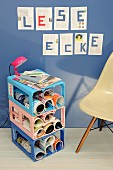 Side table with magazine compartments made from plastic drinks crates in 3 colours; pages of book on wall with letters spelling 'Reading corner' in German