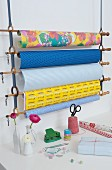 Gift wrap rack made from curtain rods and rings held in cotton loops