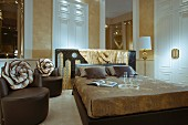 Double bed next to brown, designer leather armchairs, tall interior doors, and structured, gold stucco lustro walls