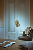 Bed, white double doors with ornamental moulding and decadent door handle and brown, designer leather armchair