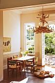 Esstisch mit verschiedenen Stühlen und Hund am Boden, im Hintergrund offene Terrassentür mit Blick in sommerlichen Innenhof