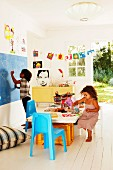 Children playing on table and drawing on chalkboard in decorated children's bedroom with open door leading to garden