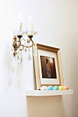 Framed photograph and colourful toy cars on floating shelf next to candle sconce with glass pendants