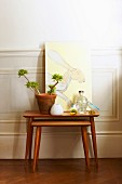 Two-piece set of wooden side tables, arrangement of potted plant and picture of hare against white wainscoting