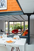 Open-plan living area with white dining table, corner sofa and designer armchair in front of sliding terrace doors