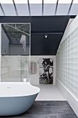 Elegantes minimalistisches Badezimmer mit Glasbausteinwand und Designerwanne