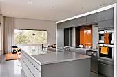 Moderne offene Küche in Hellgrau mit orangefarbenen Farbakzenten