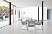 Essbereich in minimalistischem Luxusambiente mit Stahlstützen und Blick auf Pool