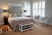 Country-house-style bedroom with bench at foot of double bed and white wicker chairs