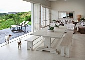 Rustic dining table and wooden benches next to sliding folding doors leading to terrace