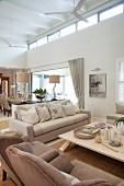 Offener, hell möblierter Wohnraum mit Sitzgruppe und Couchtisch, Essplatz im Hintergrund