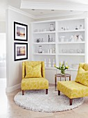 Yellow easy chairs and side table on round rug in front of white ornaments on white shelving
