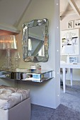 Floating dressing table mounted on wall below mirror with curving silver frame